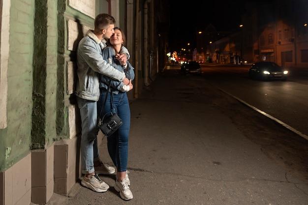 男は彼のガールフレンド、バックグラウンドで夜の街を抱擁します。夜の街で恋をしている幸せな若いカップル。路上でロマンチックなデート