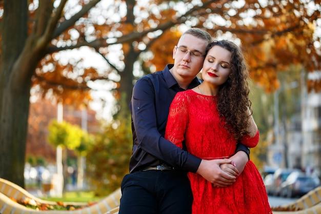 秋の街の路地で黒いシャツを着た男と赤いドレスを着た女の子