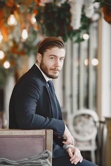 검은 양복을 입은 남자. 레스토랑에서 남성.