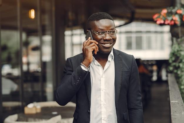 검은 양복을 입은 남자. 휴대 전화를 가진 남자입니다. 사무실에서 사업가입니다.