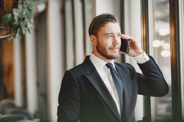 黒のスーツを着た男。携帯電話を持つ男性。オフィスのビジネスマン。 無料写真