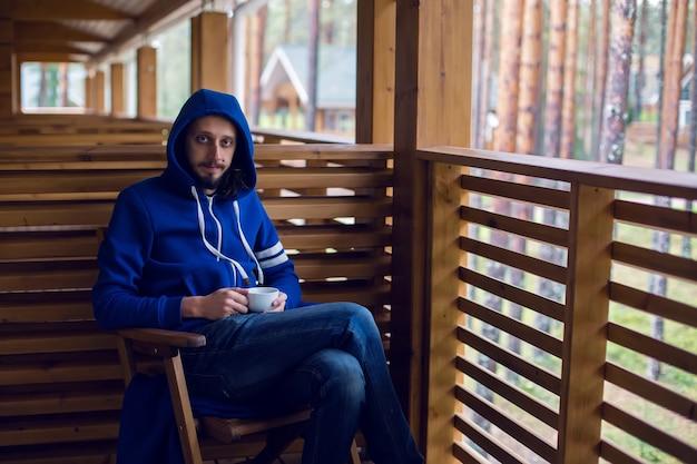 Парень в синей куртке с накинутым на голову капюшоном сидит на стуле на балконе с чаем в руке