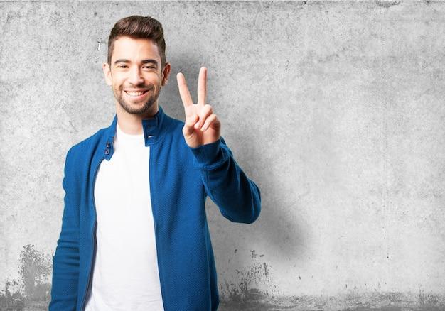 勝利の指で青色のジャケットでガイ
