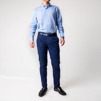Парень в классической синей рубашке и синих брюках.