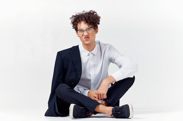 古典的なスーツを着た男は、顔の明るい部屋の眼鏡で床に座っています