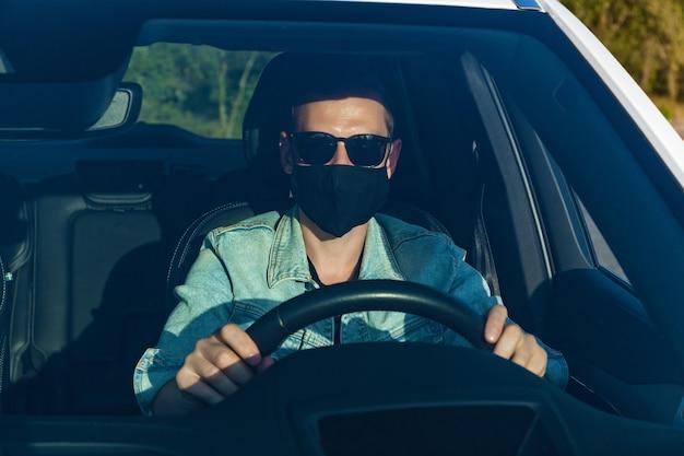 차를 운전하는 얼굴에 마스크를 쓴 데님 재킷과 검은 안경을 쓴 남자