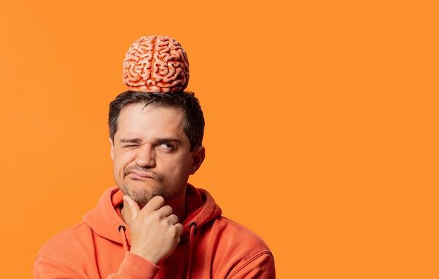 Парень в толстовке с мозгом на голове думает о чем-то на оранжевом