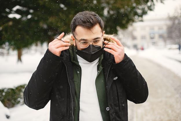 マスクの男。暖かい服を着たインド人。冬の路上で男。
