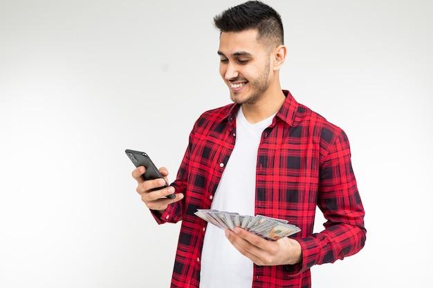 格子縞のシャツを着た男は、コピースペースのある白い背景に電話でお金を獲得したと報告しています。