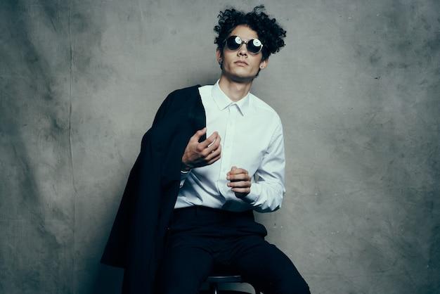 スーツを着た男が室内の椅子に座り、顔に眼鏡をかけ、手にジャケットを持っている