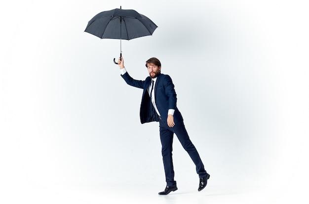 Парень в костюме с зонтиком в руке на светлом фоне ветреной погоды
