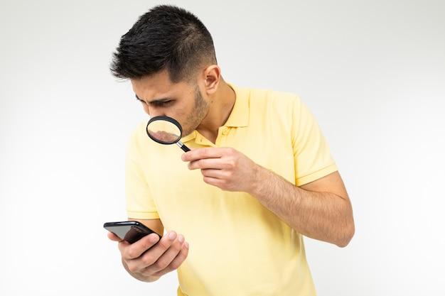 Парень в футболке смотрит через увеличительное стекло на телефон в руке на белом фоне.