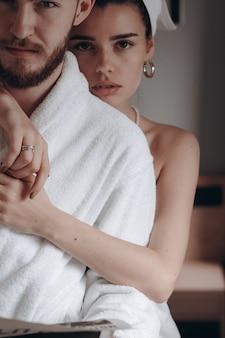 Парень в белом халате и женщина в полотенце