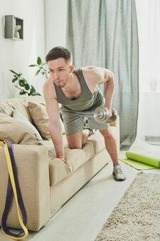 Парень в спортивной одежде, опираясь на диван во время тренировки с гантелями для рук и бицепсов во время тренировки дома утром