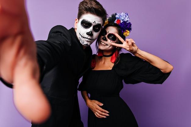검은 색 클래식 재킷을 입은 남자가 셀카를 찍고 얼굴이 그려진 여자 친구가 평화 표시를 보여줍니다.