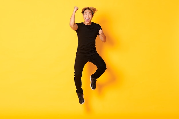 黒い服を着た男がジャンプして勝利を祝う