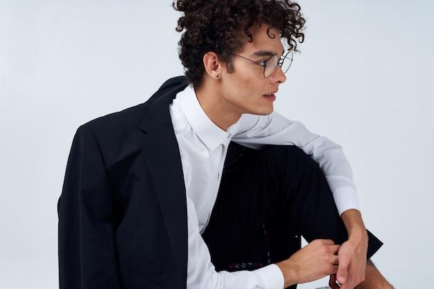 床に座っている黒いジャケットの男ファッションエレガントなスタイル。高品質の写真