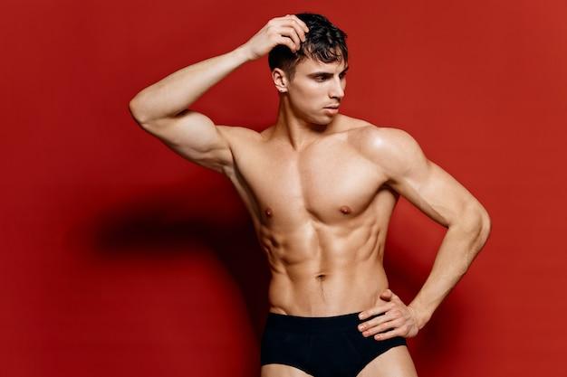 黒のショートパンツの男は、赤い背景のポーズモデルの胴体に彼の頭に手を保持します