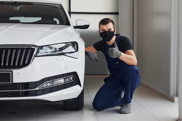 Парень в синей форме и черной защитной маске сидит возле белого автомобиля и показывает большой палец вверх