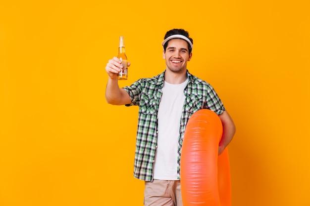 隔離されたスペースにビールとオレンジ色の膨脹可能な円のボトルを保持しているキャップと白いtシャツの男。