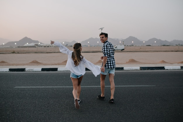 デニムのショートパンツを着た男とトレンディなブラウスを着た長髪の女性が道路を横切って走り、山の景色を楽しんでいます。高速道路を歩いて、夏に外で楽しんで手を繋いでいる若いカップルを笑ってください。