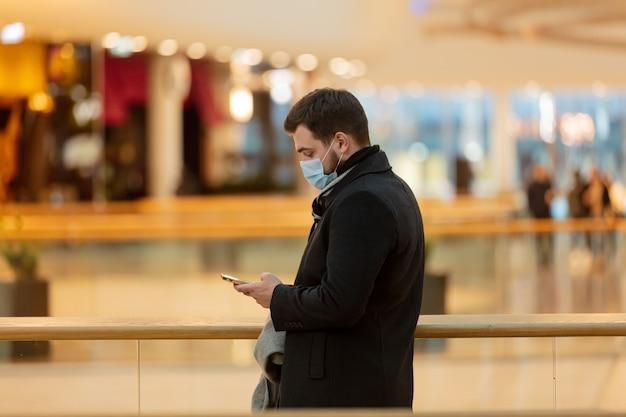 Парень в маске и пальто использует мобильный телефон в городском торговом центре во время пандемии
