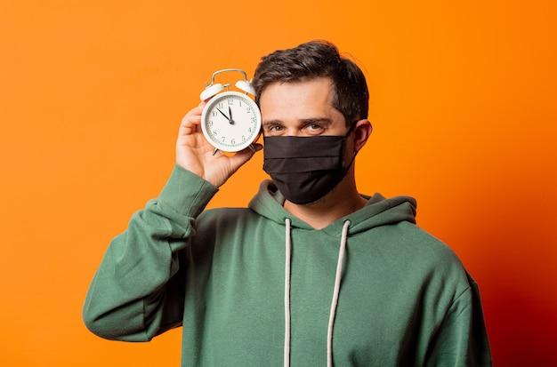 オレンジ色の目覚まし時計とフェイスマスクと緑のパーカーの男