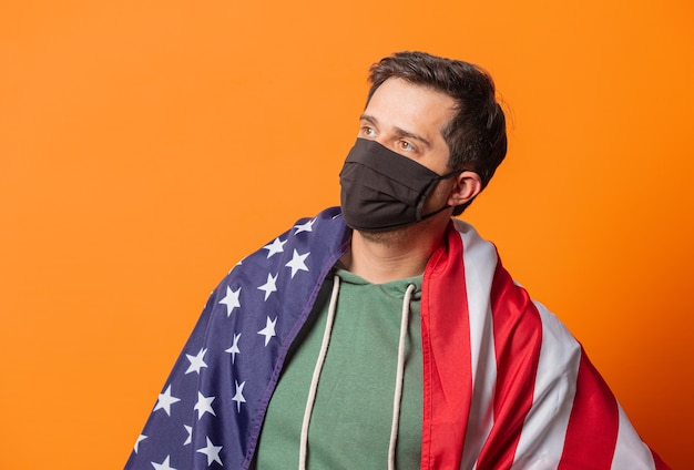 Парень в маске и зеленом худи с флагом сша на оранжевом