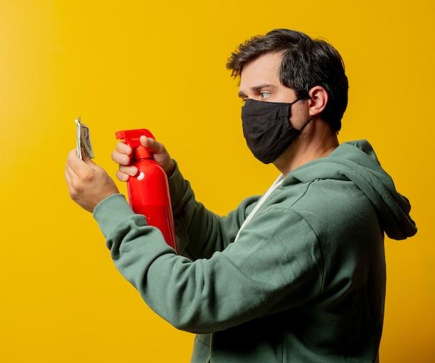 안면 마스크에있는 남자는 노란색에 소독 스프레이와 돈을 잡아