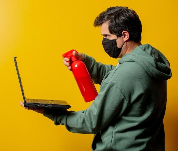 Парень в маске держит дезинфицирующий спрей и блокнот на желтом