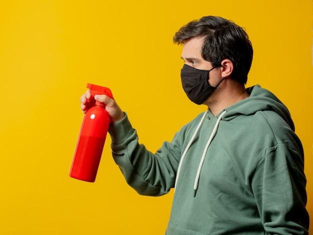 Парень в маске держит дезинфицирующий спрей на желтом