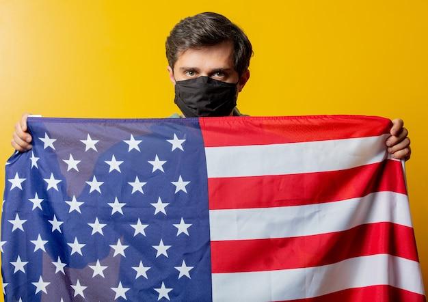Парень в маске держит флаг сша на желтом