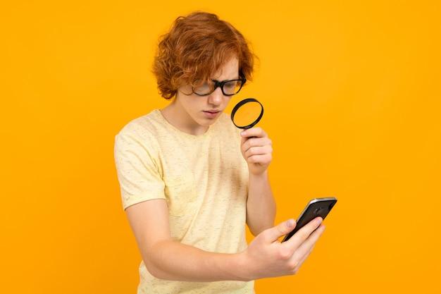 拡大鏡を手に持つメガネの男は、黄色の背景に彼の手でスマートフォンを見てください。新しいビジョンのコンセプト