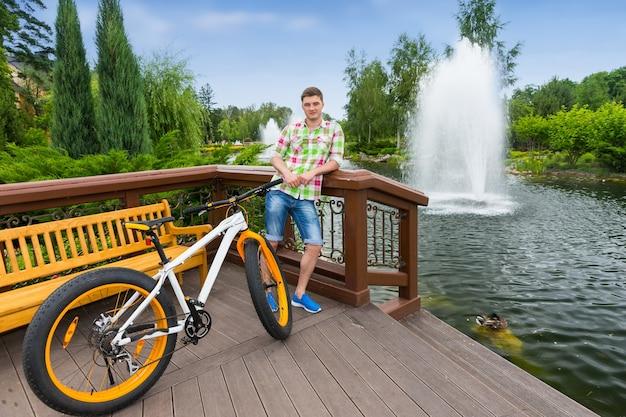 배경에 분수가 있는 공원에서 자전거를 탄 후 나무 데크에 서 있는 난간에 기대어 녹색 및 빨간색 격자 무늬 셔츠를 입은 남자
