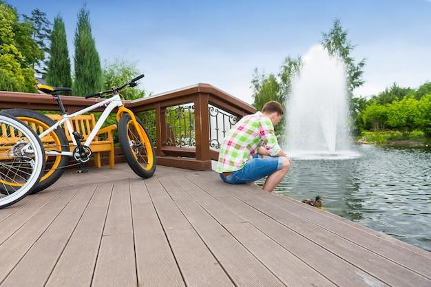 배경에 분수가 있는 공원에서 자전거를 탄 후 나무 데크에 앉아 있는 녹색 및 빨간색 격자 무늬 셔츠를 입은 남자