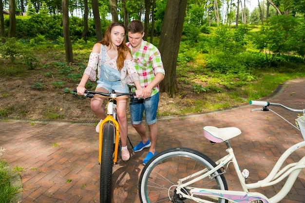 녹색과 빨간색 격자 무늬 셔츠를 입은 남자는 공원이나 숲에서 자전거를 타는 여자 친구를 가르칩니다.