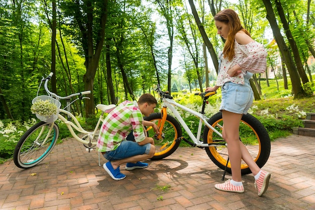녹색과 빨간색 체크무늬 셔츠를 입은 남자가 공원에서 자전거를 타고 자전거를 수리하려고 하는 동안 여자친구가 과정을 감독합니다