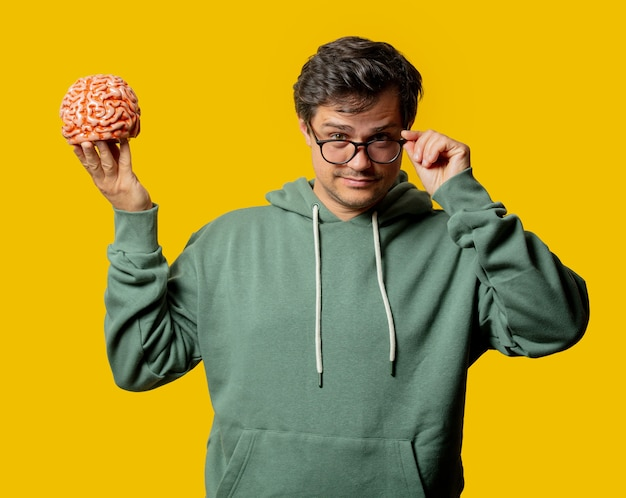 Парень в зеленой толстовке с мозгом на желтом