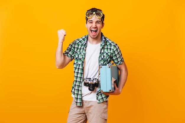 緑のシャツとベージュのショートパンツを着た男は、感情的に喜び、拳を握り締めます。ダイビングマスク、レトロなカメラ、スーツケースを持った男がオレンジ色の空間で笑います。