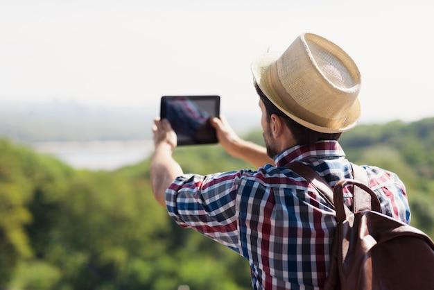 모자를 쓰고 여행을위한 배낭을 쓴 남자는 사진을 찍습니다.