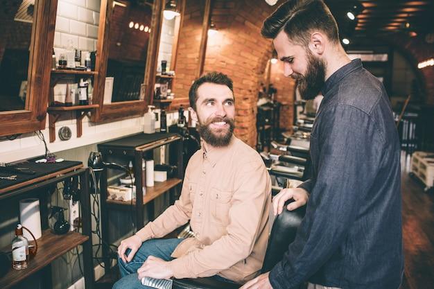 Парень в розовой рубашке сидит в кресле и смотрит на парня в синей рубашке. он счастлив видеть его. другой парень смотрит на пол.