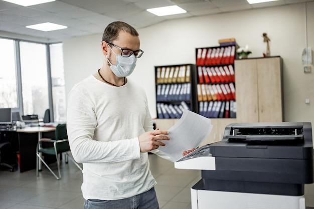 防護マスクの男は文書をコピーします