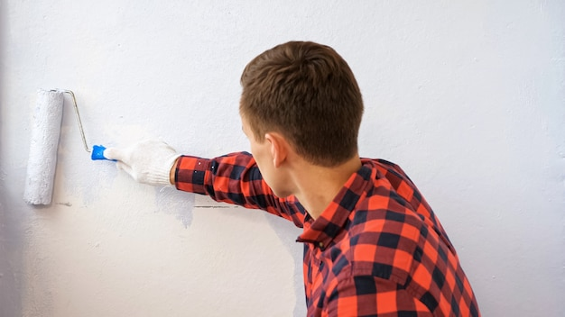 赤い市松模様のシャツの男は、家の裏側のビューでモダンで広々とした艶をかけられたロッジアの修理を行うライトグレーの色で壁をペイントします