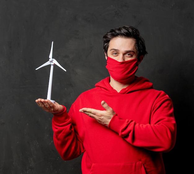 빨간 셔츠와 얼굴 마스크를 입은 남자가 어두운 벽에 작은 풍력 발전기를 들고