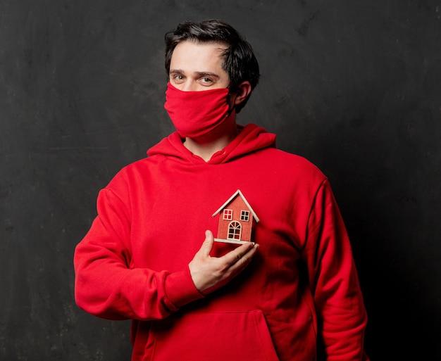 赤いスウェットシャツとフェイスマスクの男は暗い壁におもちゃの家を保持します