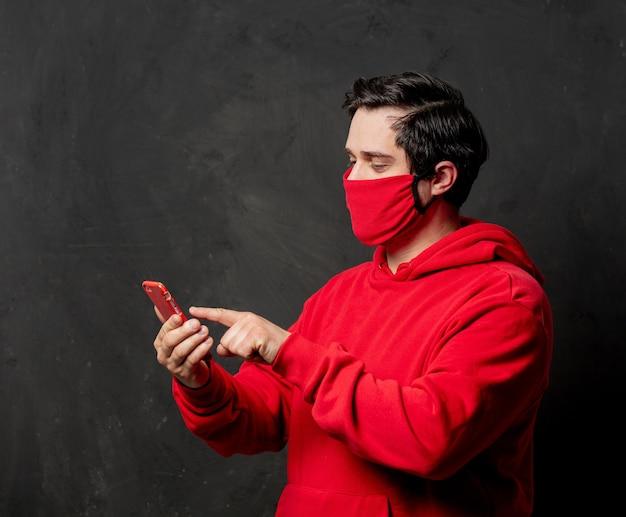 暗い壁に携帯電話を使用して赤いスウェットシャツとフェイスマスクの男