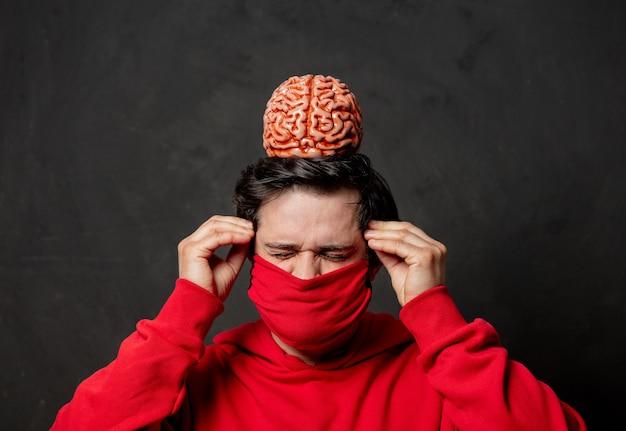 Парень в красной толстовке и маске с мозгом на темной стене
