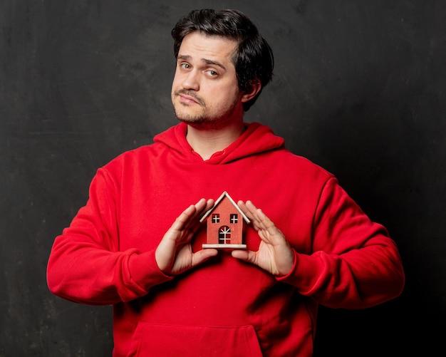 赤いスウェットシャツの男は暗い壁に小さな家を保持します