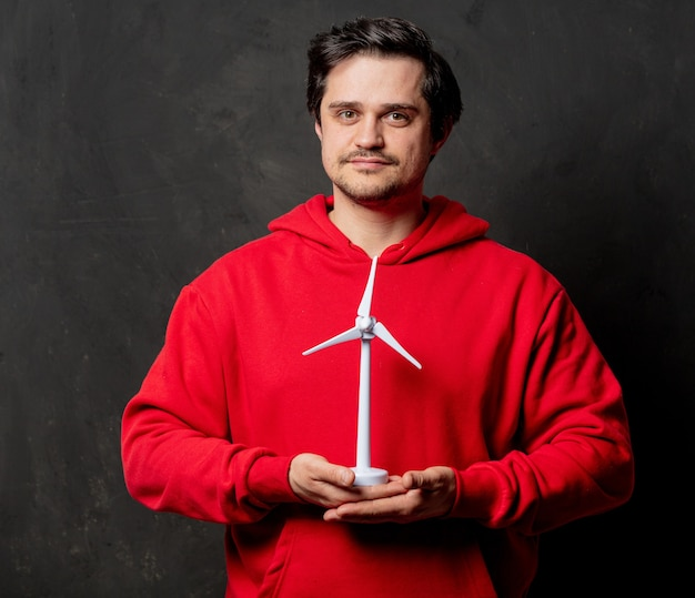 빨간 셔츠를 입은 남자가 어두운 벽에 작은 풍력 발전기를 잡아