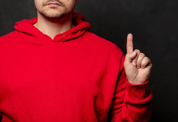 Парень в красной толстовке показывает жест пальцем на темной стене